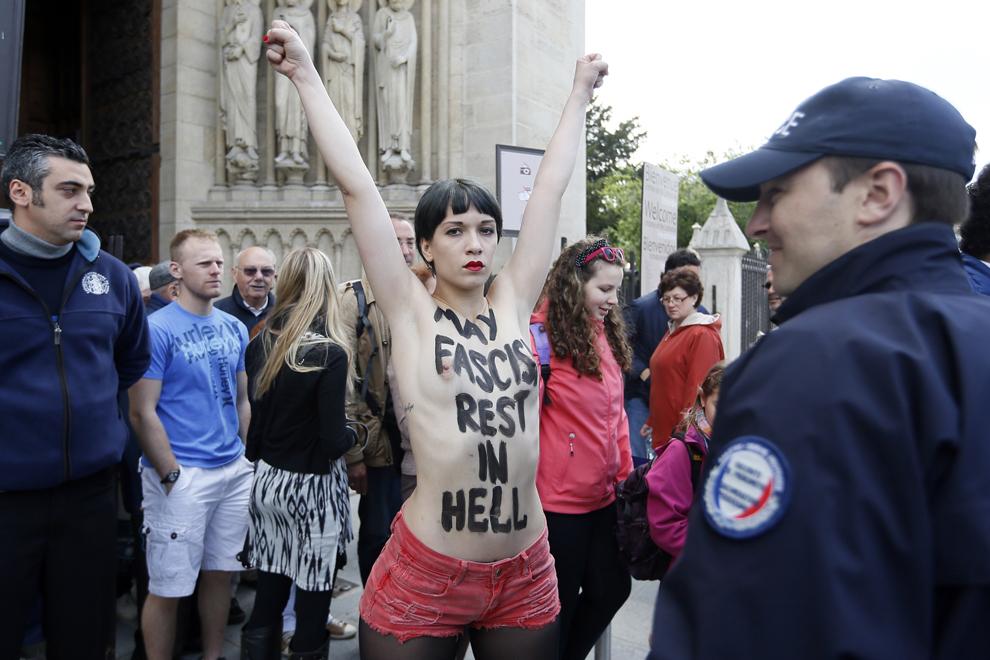 """O membră a grupului Femen purtând pe piept textul """"Fasciştii să se odihnească în iad"""" gesticulează înainte de a fi arestată de politie după ce a luat parte la un protest organizat în catedrala Notre Dame din Paris, miercuri, 22 mai 2013."""