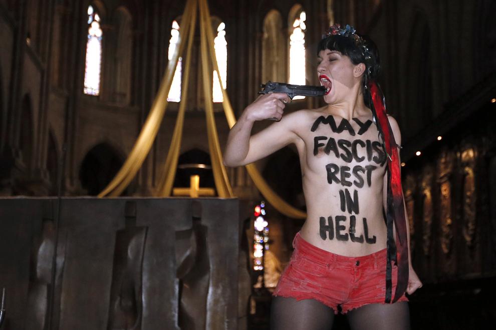 """O membră a grupului Femen purtând pe piept textul """"Fasciştii să se odihnească în iad"""" ţine în mână o armă de jucărie, în timp ce ia parte la un protest organizat în catedrala Notre Dame din Paris, miercuri, 22 mai 2013."""