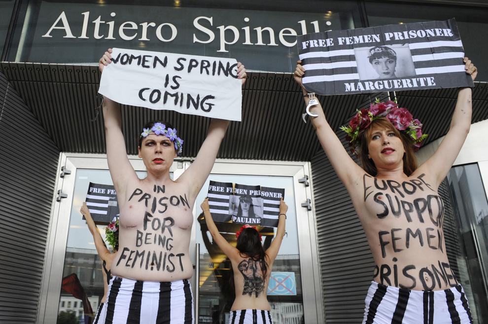 Membre ale organizaţiei Femen protestează topless ţinând în mâini pancarte, în faţa Parlamentului European, la Bruxelles, miercuri, 12 iunie 2013.