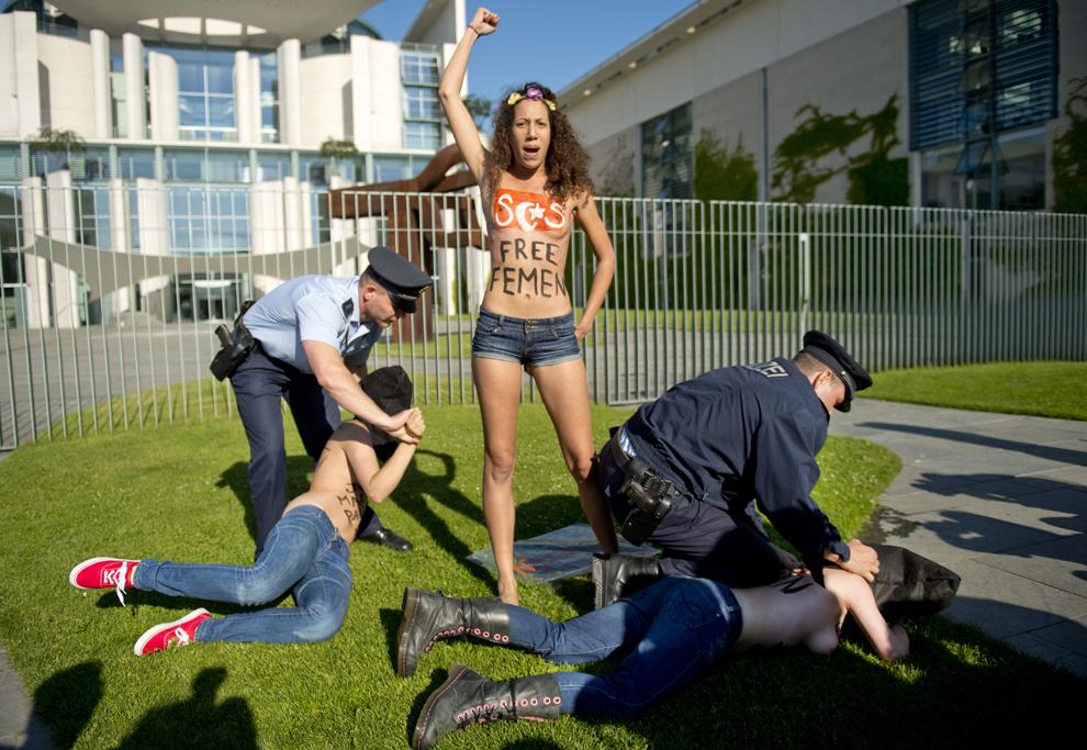 """Activiste topless, membre ale grupării feministe Femen, sunt arestate în timp ce strigă """"Merkel, Elibereaza Femen"""", în Berlin, vineri, 7 iunie 2013."""