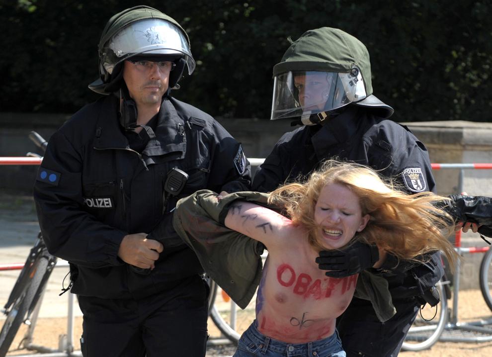 Poliţişti reţin o activistă topless din grupul feminist Femen, care protesta împotriva politicilor presedintelui Obama, aflat în vizita la Berlin, miercuri, 19 iunie 2013.