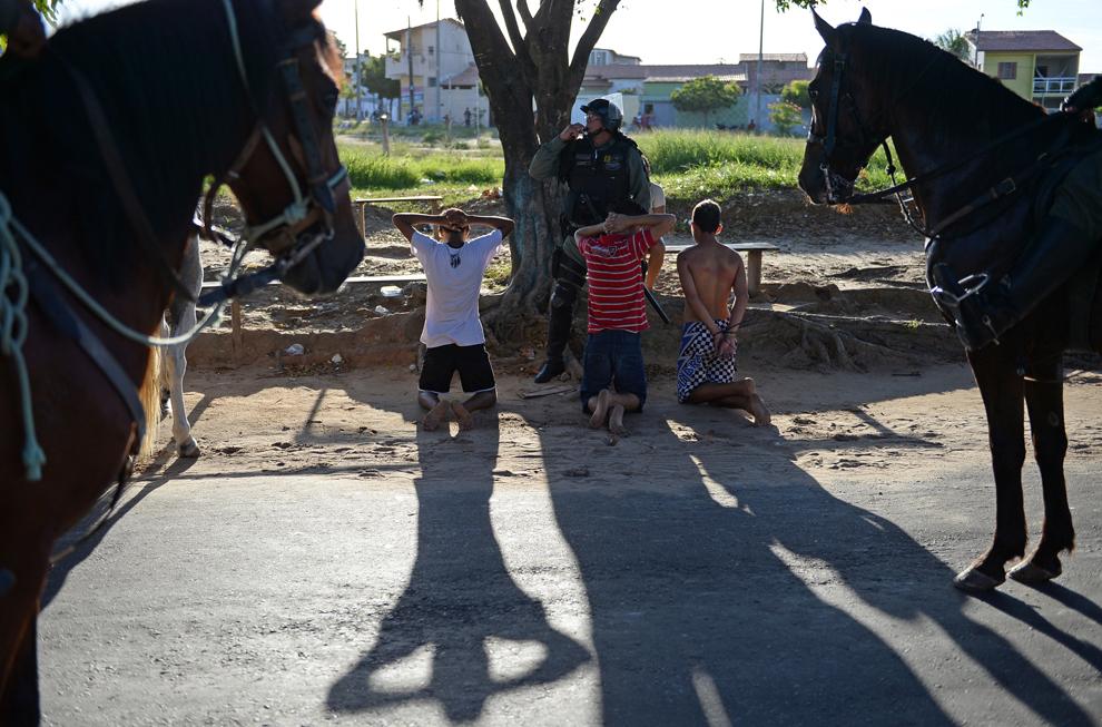 Mai mulţi poliţişti păzesc un grup de bărbaţi, după o demonstraţie violentă desfăşurată în perimetrul de securitate de 2 km din jurul stadionului Castelao din Fortaleza, unde naţionalele de fotbal ale Spaniei şi Italiei au jucat în semifinala Cupei Confederaţiilor 2013, joi, 27 iunie 2013.