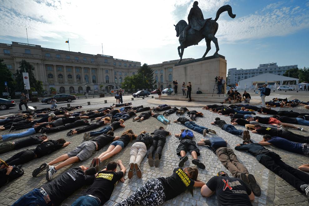 Mai mulţi români stau întinşi pe pavaj în timpul unui flash mob, în Bucureşti, vineri, 28 iunie 2013. Aproape 50 de persoane au stat nemişcate pentru câteva minute în jurul statuii Regelui Carol I pentru a comemora anexarea teritoriilor româneşti de către Uniunea Sovietică, pe 28 iunie 1940, în timpul celui de-al Doilea Război Mondial.