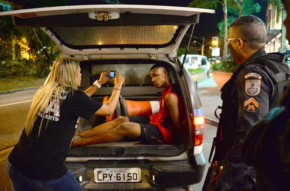 O femeie care a fost jefuită îl fotografiază pe unul dintre hoţi, după ce acesta a fost arestat de poliţişti, în timp ce protestari anti-guvernamentali demonstrează în Rio de Janeiro, vineri, 28 iunie 2013.