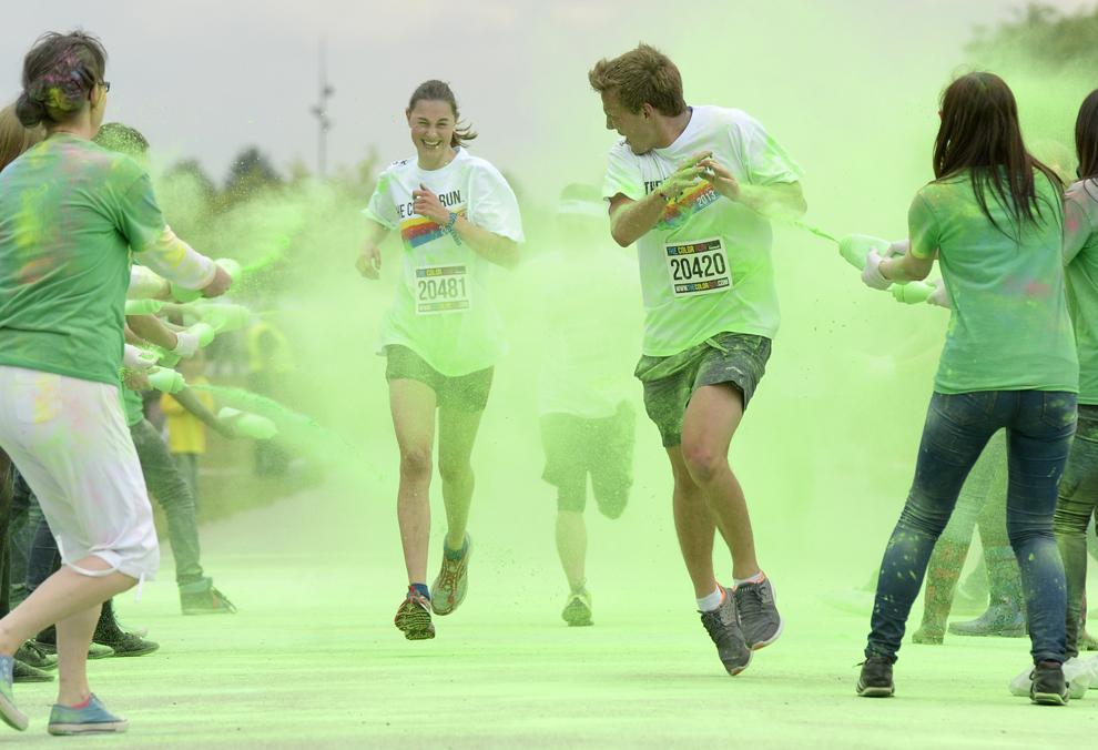 Participanţi la alergarea colorată reacţionează în timp ce sunt împroşcaţi cu pudră verde, în Munchen, duminică, 30 iunie 2013. Mii de alergători au participat la alergarea colorată, pe o distanţă de 5 km, trecând prin 4 zone de culoare.