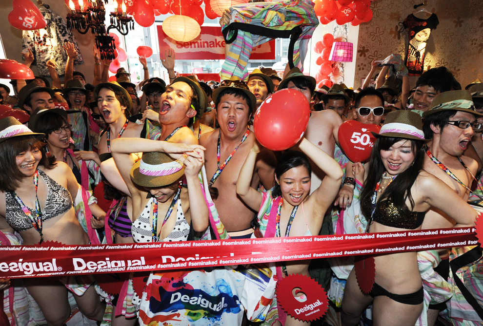 O sută de cumpărători în costume de baie participă la 'petrecerea semi-dezbrăcată', la magazinul Desigual din Tokyo, sâmbătă, 22 iunie 2013.