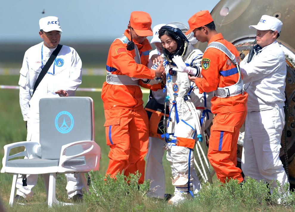 Astronauta chineză Wang Yaping (C) coboară din naveta spaţială Shenzhou-10, care a aterizat pe o pajişte din regiunea Mongolia Interioara din nordul Chinei, după o misiune de 15 zile in spaţiu, miercuri, 26 iunie 2013.