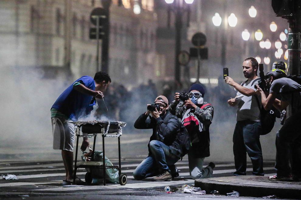 Un student pregăteşte un grătar pe o stradă din apropierea primăriei din Sao Paulo, în Brazilia, marţi, 18 iunie 2013. Preşedintele Braziliei, Dilma Rousseff, a promis marţi că va asculta tinerii care participă la cele mai mari proteste din această ţară din ultimii 20 de ani, urmare a nemulţumirilor legate de costurile uriaşe ale organizării unor evenimente precum Cupa Mondială la fotbal.