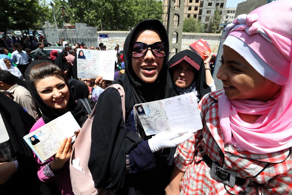 Femei iraniene îşi arată documentele de identitate în timp ce stau la coadă pentru a vota în primul tur al alegerilor prezidenţiale, la o secţie de votare din Teheran, vineri, 14 iunie 2013.