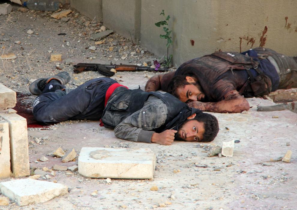 Doi luptători rebeli răniţi se ascund de tirul lunetiştilor în timp ce aşteaptă sa fie evacuaţi de către camarazii lor, în timpul unor ciocniri cu forţele pro-guvernamentale, în cartierul Suleiman al-Halabi din Alep, joi, 20 iunie 2013.
