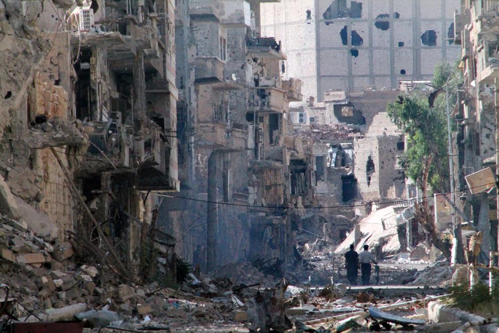 Doi sirieni merg pe o stradă distrusă de bombardamente, în centrul oraşului Deir Ezzor din nord-estul Siriei, joi, 27 iunie 2013.