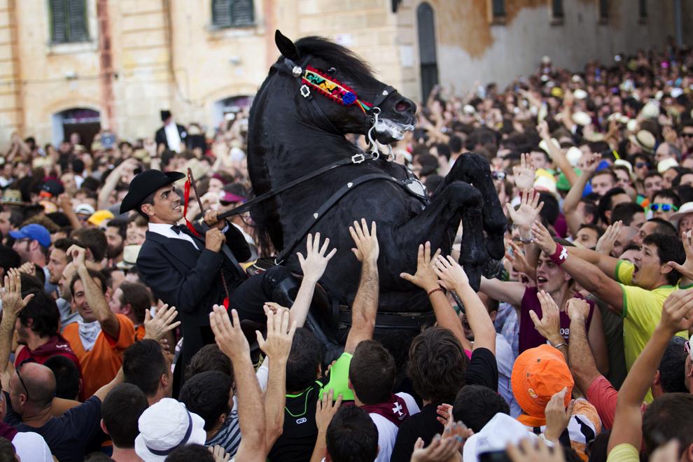 Un călăreţ îşi cabrează calul într-o mulţime de oameni, în timpul unei parade ţinute cu ocazia festivalului tradiţional de San Juan, în ajunul sărbătorii sfântului Ioan, în oraşul Ciutadella de pe insula Menorca, duminică, 23 iunie 2013.