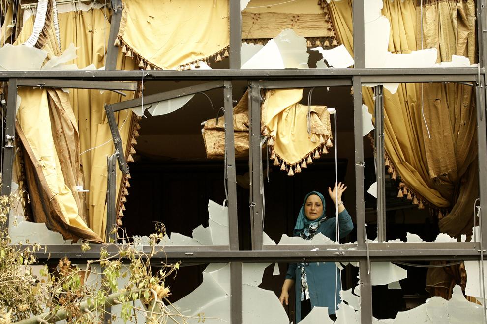 O femeie libaneză priveşte printre rămăşiţele unei ferestre distruse, în districtul Abra din oraşul sudic Sidon, în Liban, sâmbătă, 29 iunie 2013. Luptele din Abra au fost cele mai grave din Liban de la începerea conflicului din ţara învecinată, Siria.