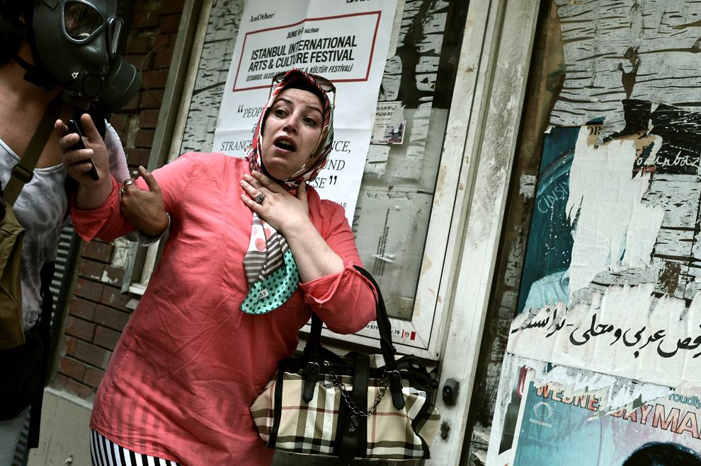 O femeie reacţionează după contactul cu gazele lacrimogene, în timpul ciocnirilor dintre protestatari şi scutieri, în piaţa Taksim din Istanbul, marţi, 11 iunie 2013.
