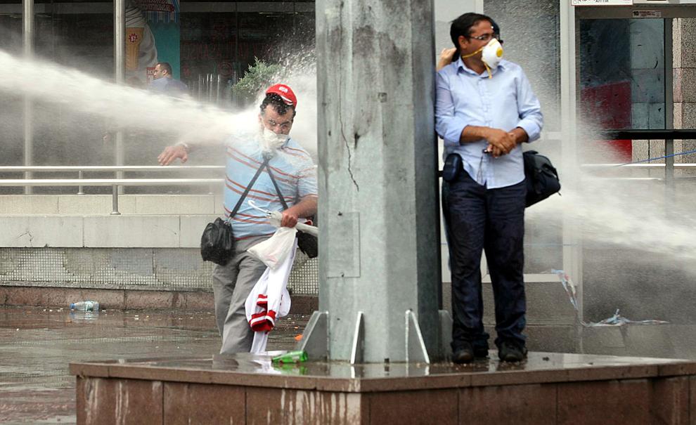 Un bărbat este lovit de jetul produs de un tun cu apă, în timpul ciocnirilor dintre scutieri şi demonstranţi, în Ankara, duminică, 15 iunie 2013.