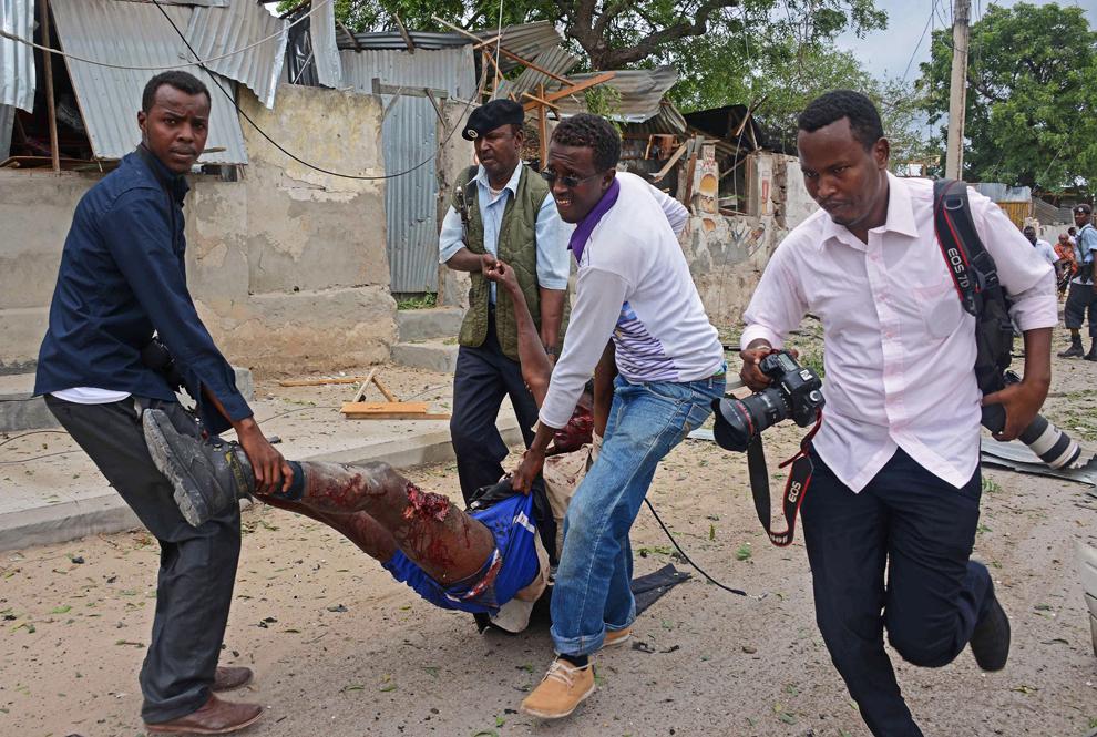 Bărbaţi somalezi transportă o persoană rănită în timpul unui atac al insurgenţilor Al-Shabaab, având legături cu Al-Qaeda, asupra bazei Naţiunilor Unite din Mogadishu, miercuri, 19 iunie 2013.