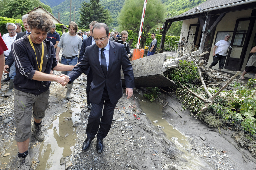 Preşedintele francez Francois Hollande merge pe o stradă din localitatea Saind-Beat, la două zile după ce aceasta a fost acoperită de o viitură, joi, 20 iunie 2013.