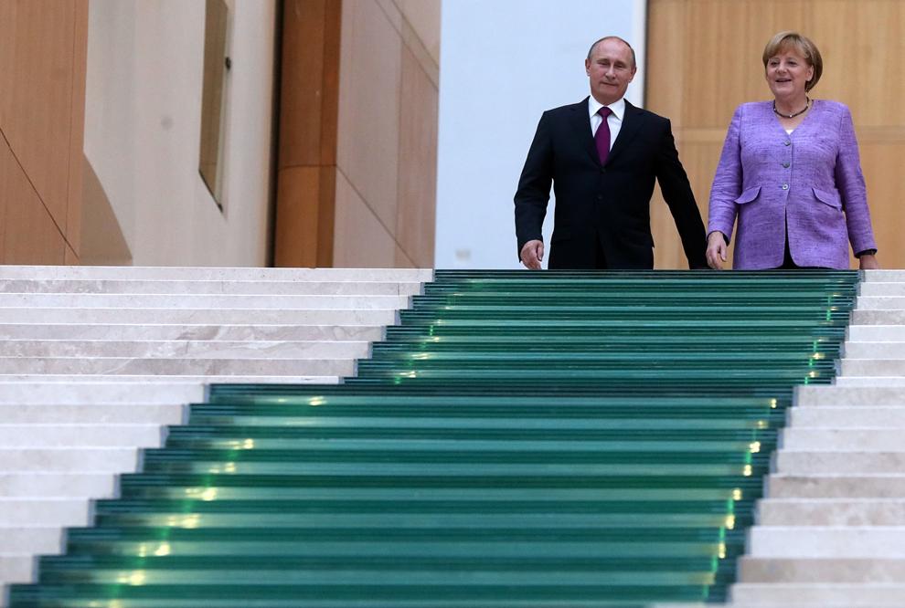 Preşedintele rus, Vladimir Putin (S), şi cancelarul german, Angela Merkel (D), coboară scările muzeului de artă State Hermitage din Sankt Petersburg, după ce au vizitat expoziţia ruso-germană 'Epoca bronzului în Europa – Europa fără graniţe', vineri, 21 iunie 2013. Expoziţia include obiecte luate de Armata Roşie din Germania, la finalului celui de-al Doilea Război Mondial.