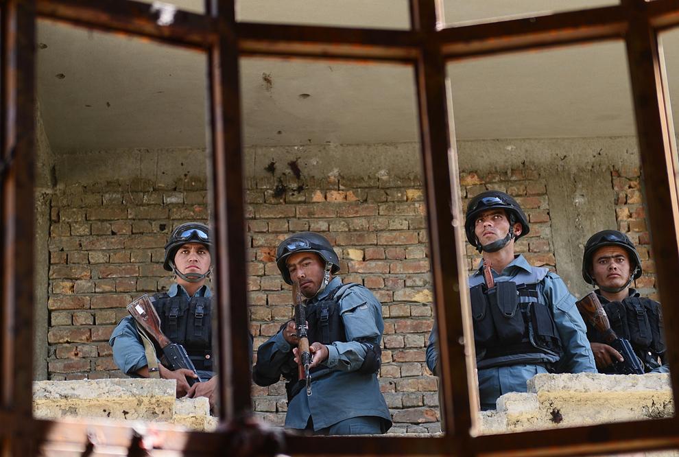 Poliţişti afgani stau de pază într-o clădire folosită de către militanţii islamişti pentru a ataca aeroportul din Kabul, luni, 10 iunie 2013. Toţi cei şapte militanţi care au lansat atacul au fost ucişi.