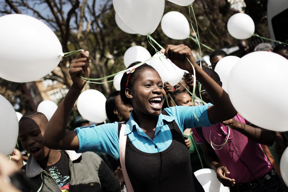 Suporteri dansează în sprijinului fostului preşedinte sud-african Nelson Mandela, în faţa spitalului Medi Clinic Heart Hospital din Pretoria, unde acesta este spitalizat, joi, 27 iunie 2013.