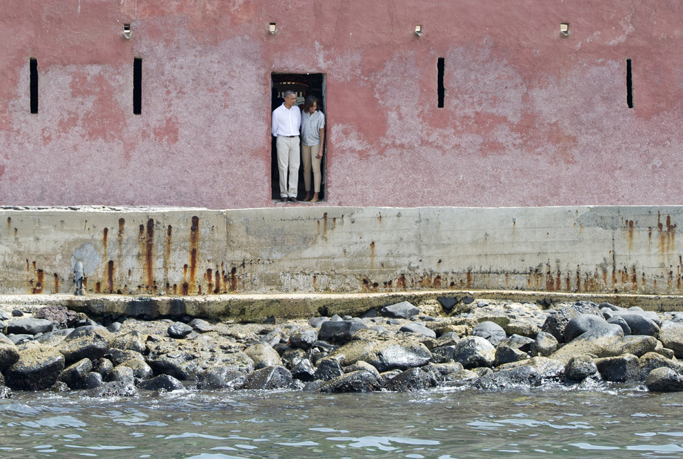 Preşedintele american Barack Obama (S) şi prima doamnă Michelle Obama privesc marea din Uşa Fără de Întoarcere, în timpul vizitării Casei Sclavilor (Maison des Esclaves) de pe insula Goree, în apropiere de coasta Dakarului, joi, 27 iunie 2013. Obama şi familia sa au vizitat muzeul amenjat în locul în care sclavii africani erau ţinuţi înainte de a trece prin uşa care îi ducea la navele cu care erau transportaţi de pe continentul african.