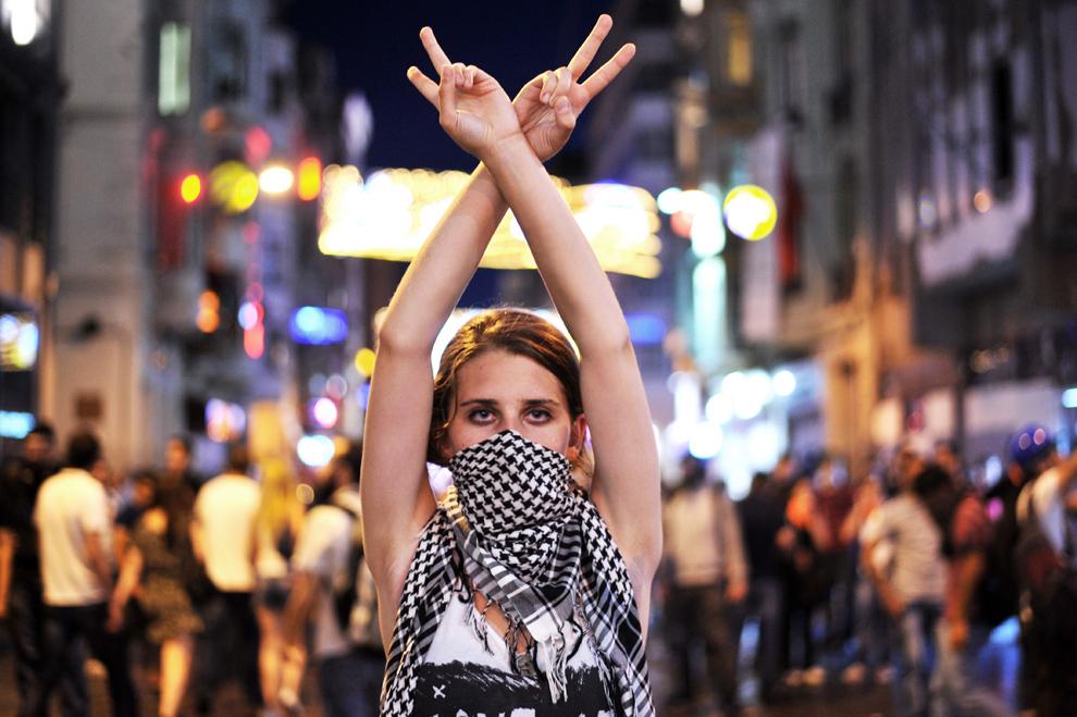 Un protestatar antiguvernamental arată semnul victoriei în timpul ciocnirilor dintre protestatari şi scutieri, în piaţa Taksim din Istanbul, duminică, 22 iunie 2013. Poliţia turcă a folosit tunurile cu apă pentru a dispersa miile de demonstranţi care s-au strâns în piaţa Taksim pentru a cere demisia premierului Recep Tayyip Erdogan.