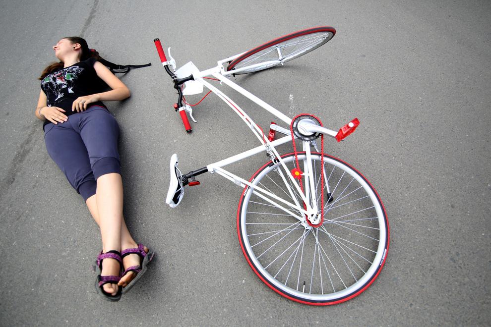 O tânără stă întinsă pe jos lângă o bicicletă aşezată pe asfalt, în timpul evenimentului Tura memorială, o campanie de susţinere a bicicliştilor sibieni, în Sibiu, sâmbătă, 1 iunie 2013.