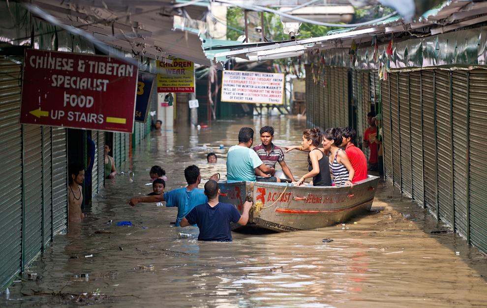Proprietarii de magazine folosesc o barcă pentru a se deplasa prin piaţa Tibetană din New Delhi, inundată de apele râului Yamuna, miercuri, 19 iunie 2013.
