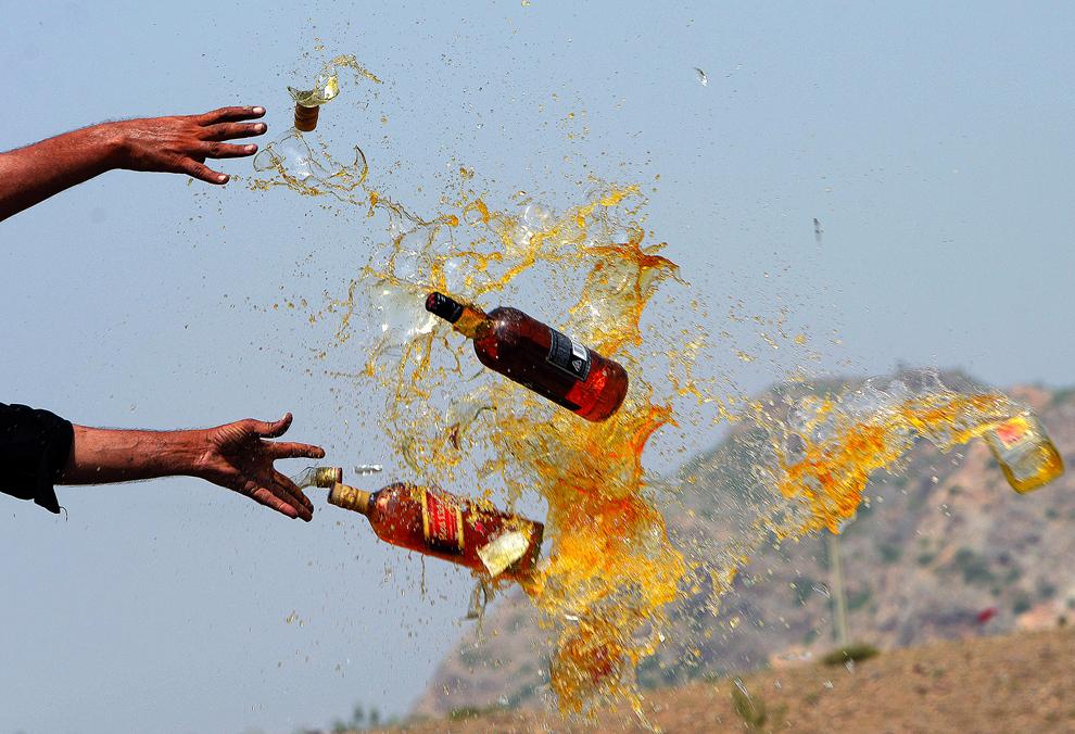 Poliţişti de frontiera pakistanezi sparg sticle cu băuturi alcoolice în cadrul unei ceremonii organizate cu ocazia Zilei Internaţionale Antidrog, în Shahkas, Pakistan, miercuri, 26 iunie 2013.