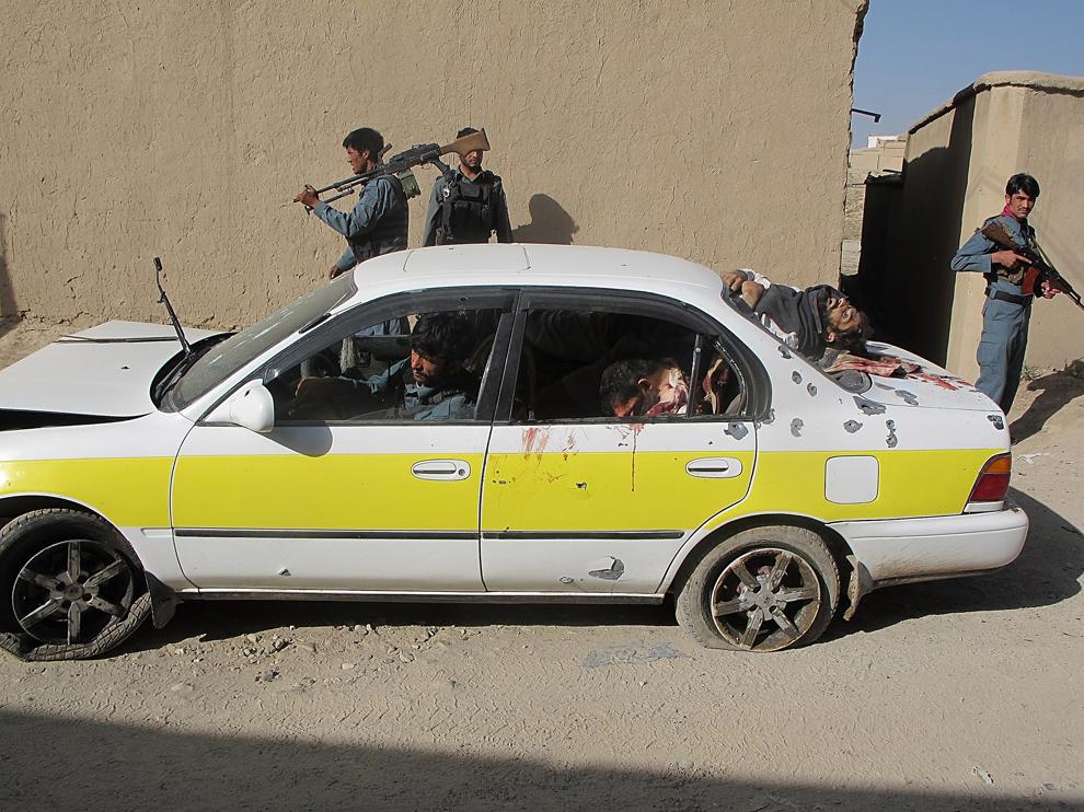 Membri ai forţelor de securitate afgane patrulează lângă o maşină în care se află corpurile unor presupuşi luptători talibani, după o ciocnire a acestora din urmă cu poliţiştii afgani, în provincia Ghazni, joi, 27 iunie 2013.