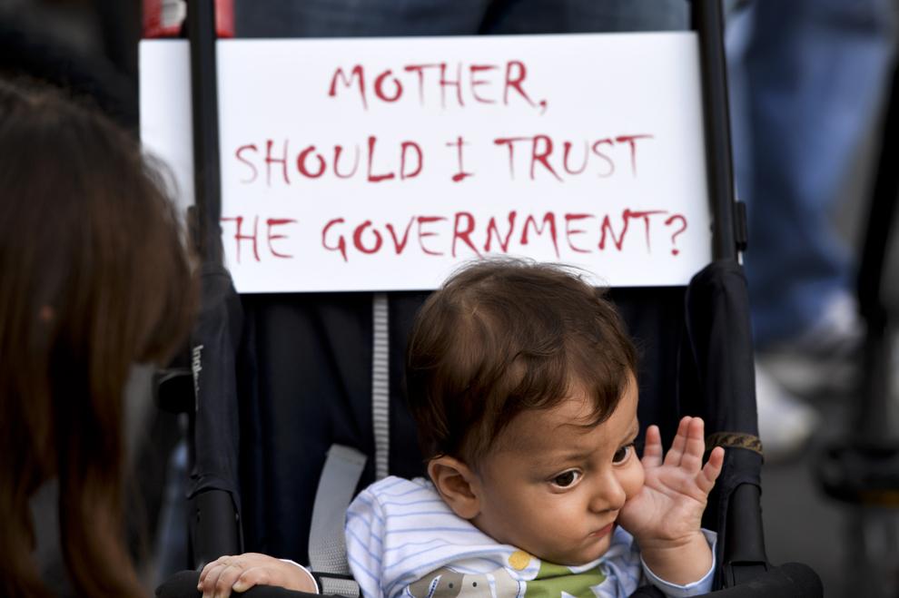 """Rareş, în vârstă de nouă luni, stă într-un cărucior unde este afişat mesajul """"Mother should I trust the government?"""", în timpul unui protest faţă de exploatarea minereurilor din perimetrul Roşia Montană, în Bucureşti, duminică, 1 septembrie 2013."""