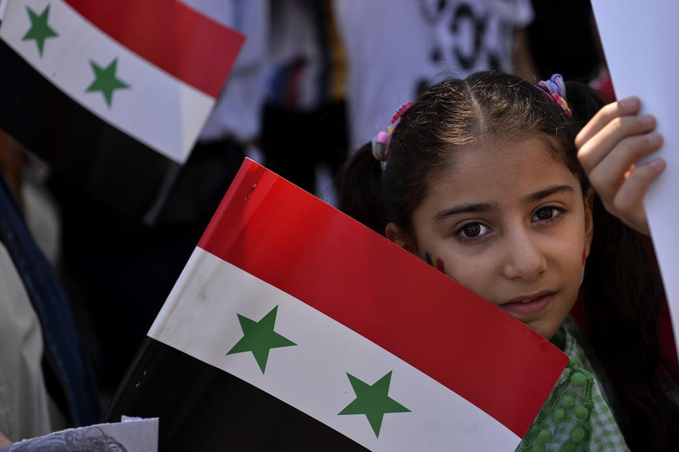 O fetiţă priveşte către cameră în timpul unui protest al sirienilor pro-Bashar al-Assad, anti-război, în Bucureşti, duminică, 1 septembrie 2013.