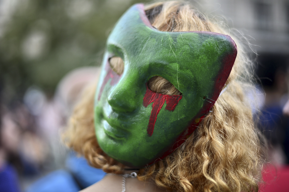 O tânără cu o mască pe cap participă la protestul faţă de exploatarea minereurilor din perimetrul Roşia Montană, în Bucureşti, luni, 2 septembrie 2013.