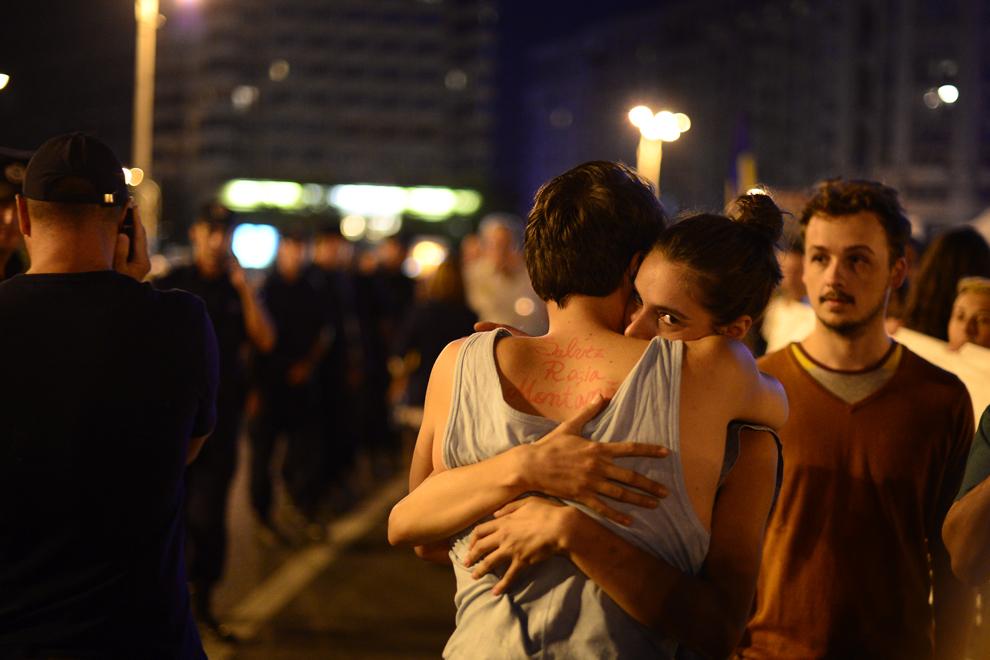 """Doi tineri se îmbrăţişează, unul dintre ei având scris pe spate textul """"Salvez Roşia Montană"""", în timpul unui protest faţă de exploatarea minereurilor din perimetrul Roşia Montană, în Bucureşti, duminică, 1 septembrie 2013."""