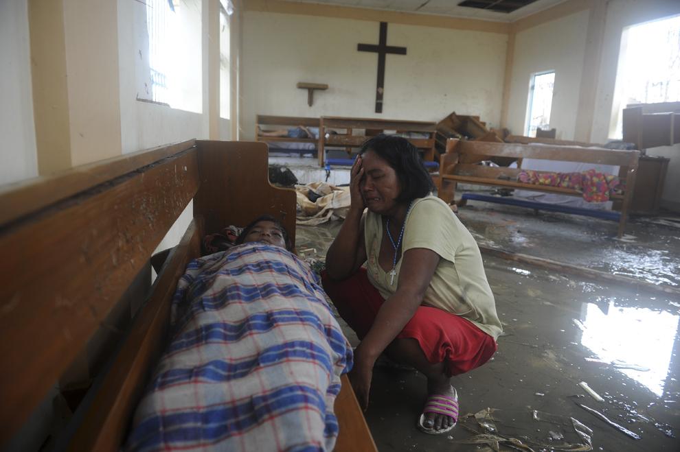 O femeie plânge lângă trupul neînsufleţit al fiului său, ce a decedat  în urma trecerii super-taifunului Haiyan, în Tacloban, provincia Leyte, Filipine, sâmbătă, 9 noiembrie 2013.