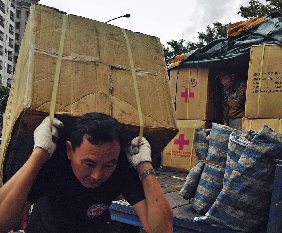 Această imagine oferită de către Societatea de Cruce Roşie din Taiwan, luni, 11 noiembrie 2013 arăta voluntari ai Crucii Roşii din Taiwan, în Taipei, transportând mărfuri destinate sinistraţilor din Filipine.