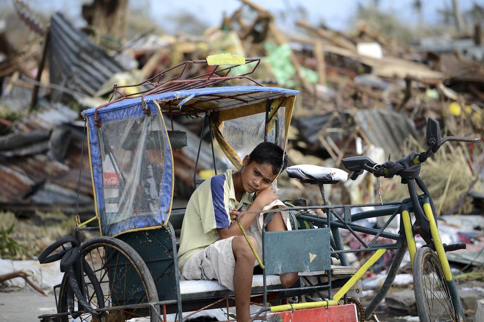 Un tânăr supravieţuitor al taifunului Haiyan se odihneşte pe o rişcă, într-o zonă devastată, luni, 11 noiembrie 2013.