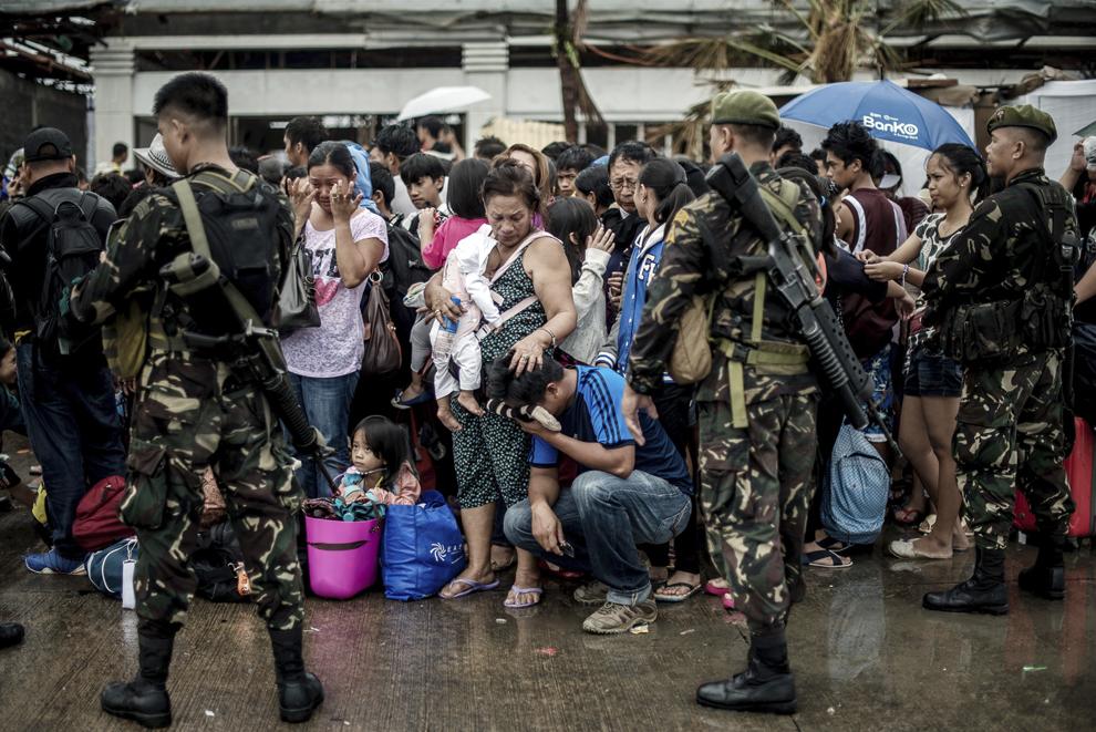 O femeie cu un copil în braţe mângâie o rudă care plânge, în timp ce supravieţuitori ai taifunului Haiyan sunt îmbarcaţi într-un avion, în timpul operaţiunilor de evacuare, pe aeroportul din Tacloban, Filipine, marţi, 12 noiembrie 2013.