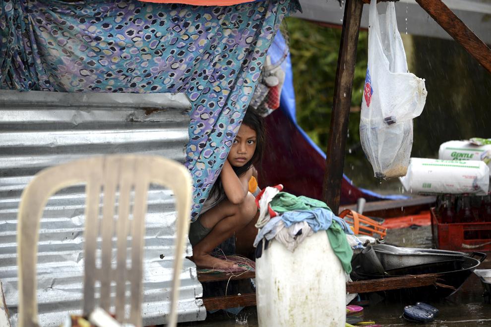 O fetiţă priveşte către aparatul de fotografiat, din interiorul unui adăpost improvizat, la trei zile de la trecerea taifunului Haiyan, în Tacloban,  provincia Leyte, Filipine, duminică, 10 noiembrie 2013.