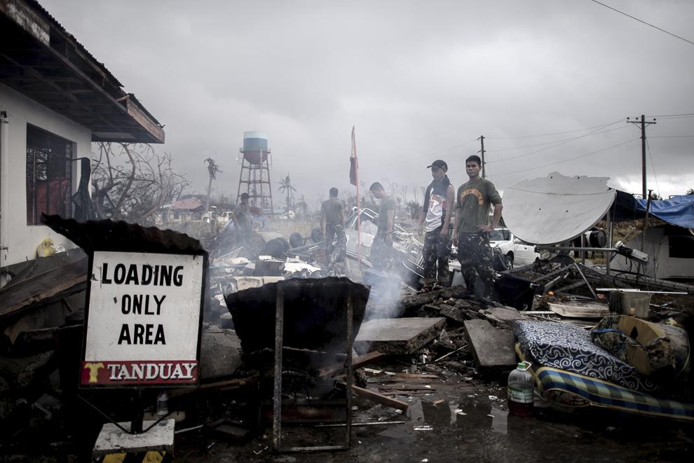 Personal militar filipinez lucrează lângă o clădire afectată de taifun Haiyan, pe aeroportul din Tacloban, Filipine, marţi, 12 noiembrie 2013.