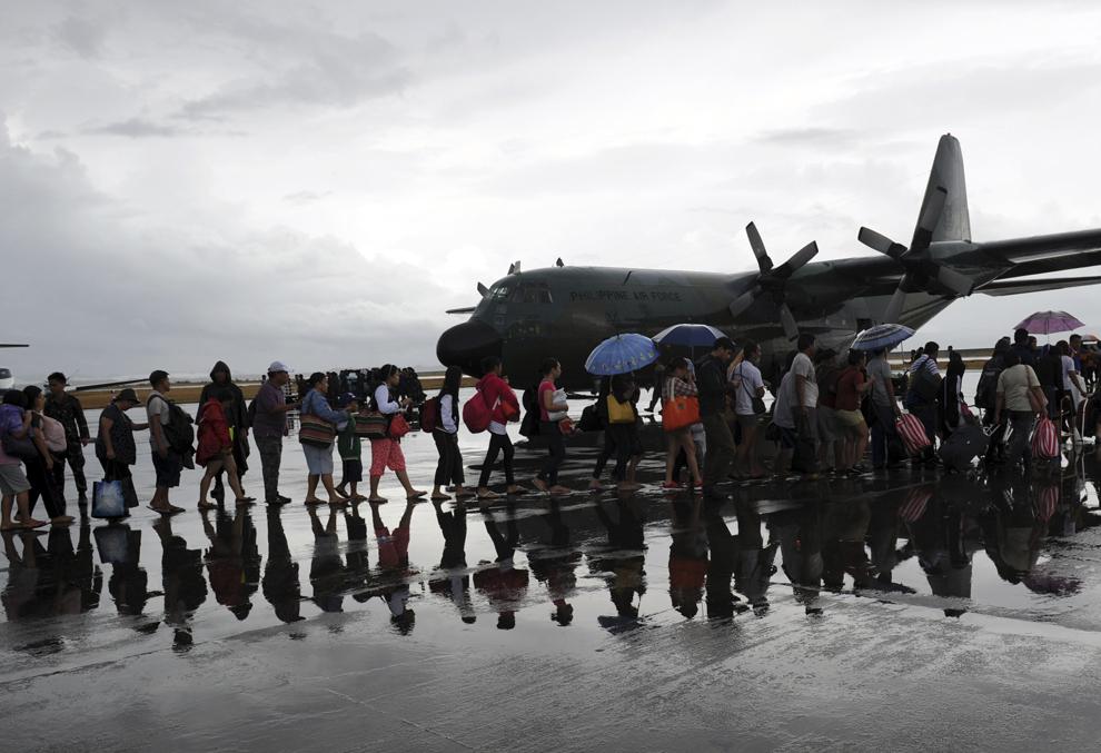 Supravieţuitorii taifunului Haiyan se îmbarcă într-un avion militar, pe aeroportul din Tacloban, Filipine, marţi, 12 noiembrie 2013.