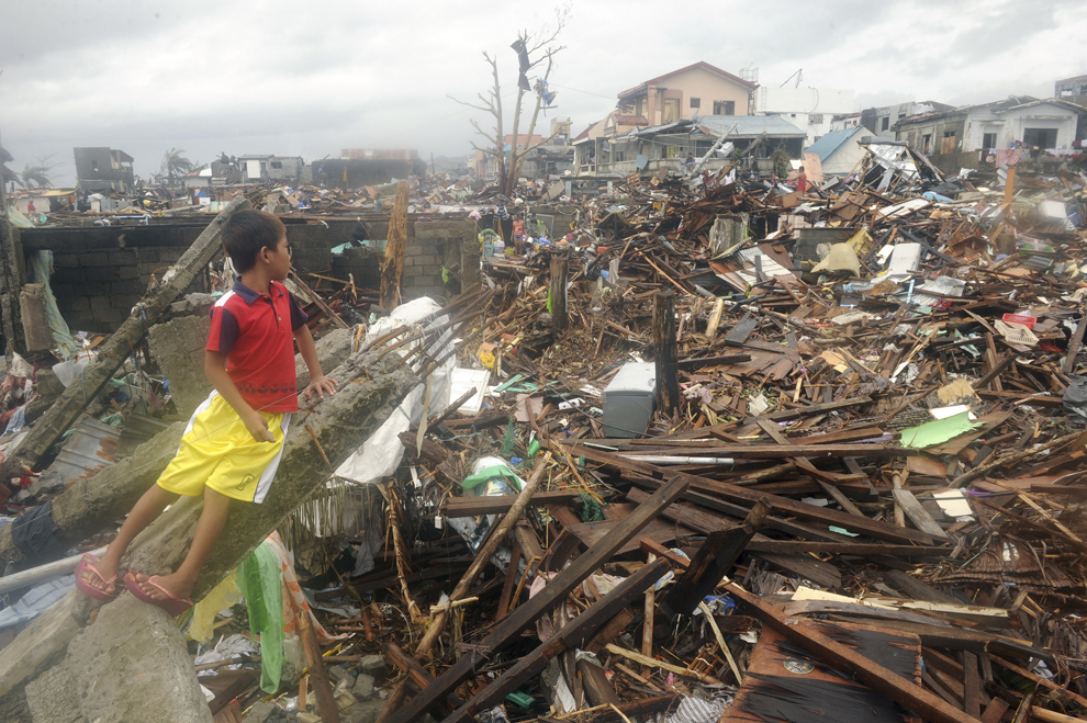 Un băiat se uită la resturile caselor distruse de taifunul Haiyan, în Tacloban, în estul insulei Leyte, marţi, 12 noiembrie 2013.