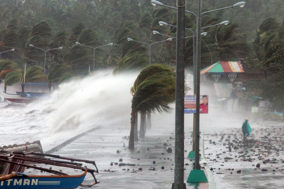 O persoană (D) se fereşte de valurile uriaşe ce se izbesc de pereţii falezei, cauzate de vânturile puternice produse de taifunul Haiyan, în oraşul Legaspi, provincia Albay, în Manila, Filipine, vineri, 8 noiembrie 2013.