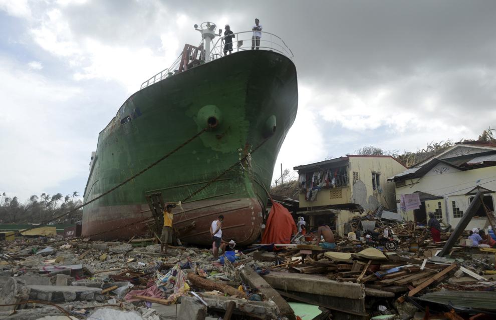 Persoane trec pe langă o navă ce a eşuat pe uscat în urma trecerii taifunului Haiyan, în Tacloban, provincia Leyte, în centru Filipine, luni, 11 noiembrie 2013.