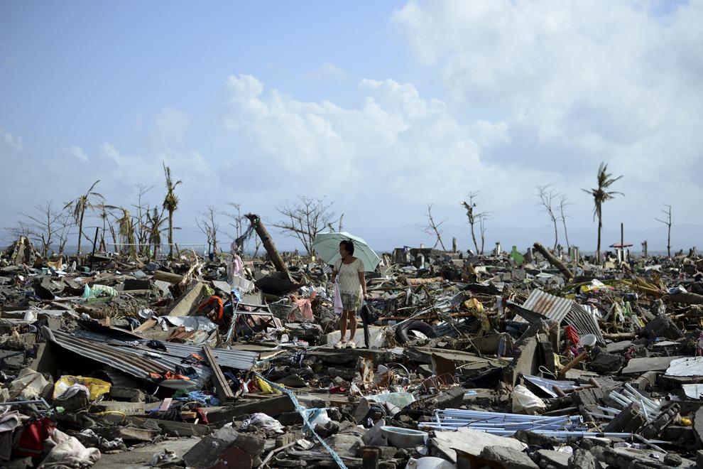 Un supravieţuitor merge printre resturile caselor distruse de către taifunul Haiyan, în Tacloban, în estul insulei Leyte, luni, 11 noiembrie 2013.