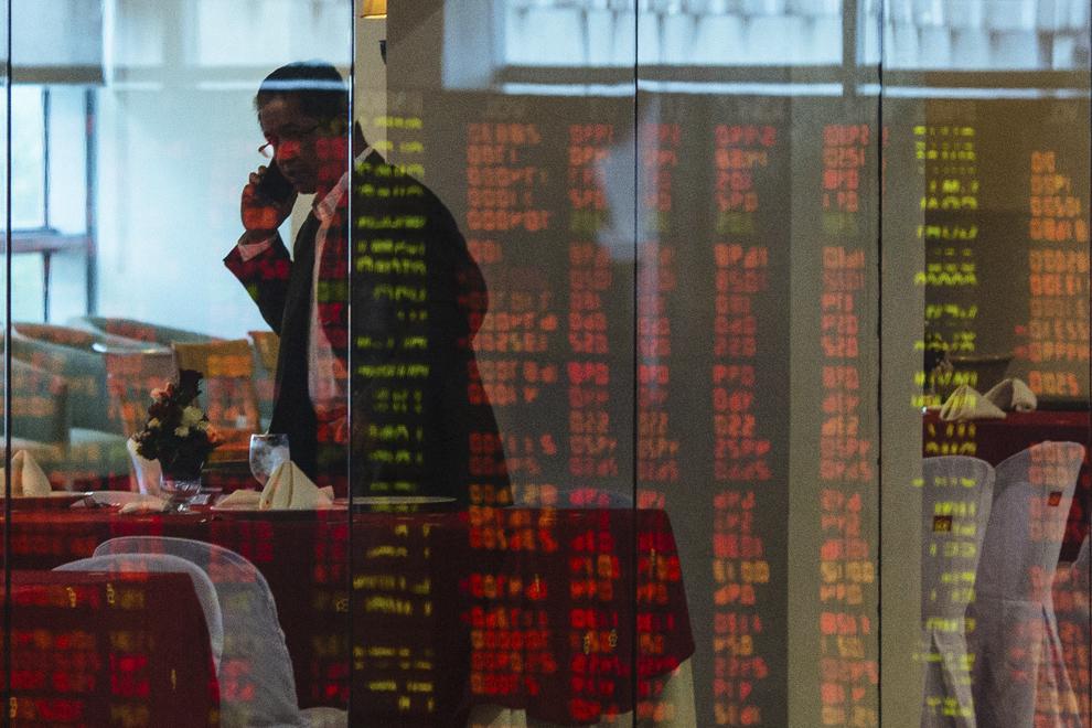 Un bărbat vorbeşte la telefon în spatele unui perete de sticlă pe care se reflectă un ecran de la bursa de valori din Manila, Filipine, luni, 11 noiembrie 2013.