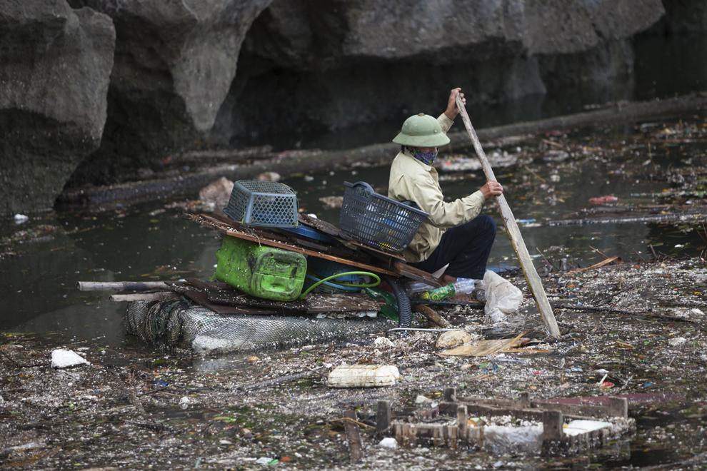 Un bărbat sortează printre resturi, materiale reciclabile, la o zi după ce super-taifunul Haiyan a ajuns pe uscat, în oraşul Halong, Vietnam, marţi, 12 noiembrie 2013.