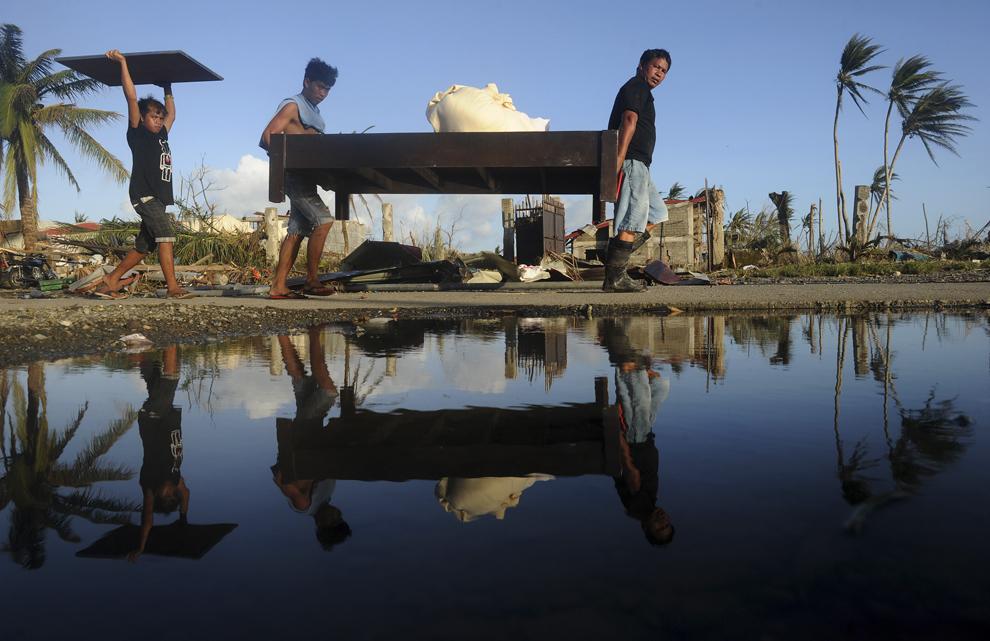 Persoane transportă mobilă ridicată dintr-un hotel din Palo, provincia Leyte, Filipine la trei zile după trecerea super-taifunului Haiyan, duminică, 10 noiembrie 2013.
