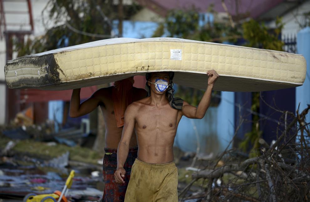 Două persoane transportă o saltea ridicată dintr-un hotel din Palo, provincia Leyte, la trei zile după trecerea super-taifunului Haiyan, duminică, 10 noiembrie 2013.