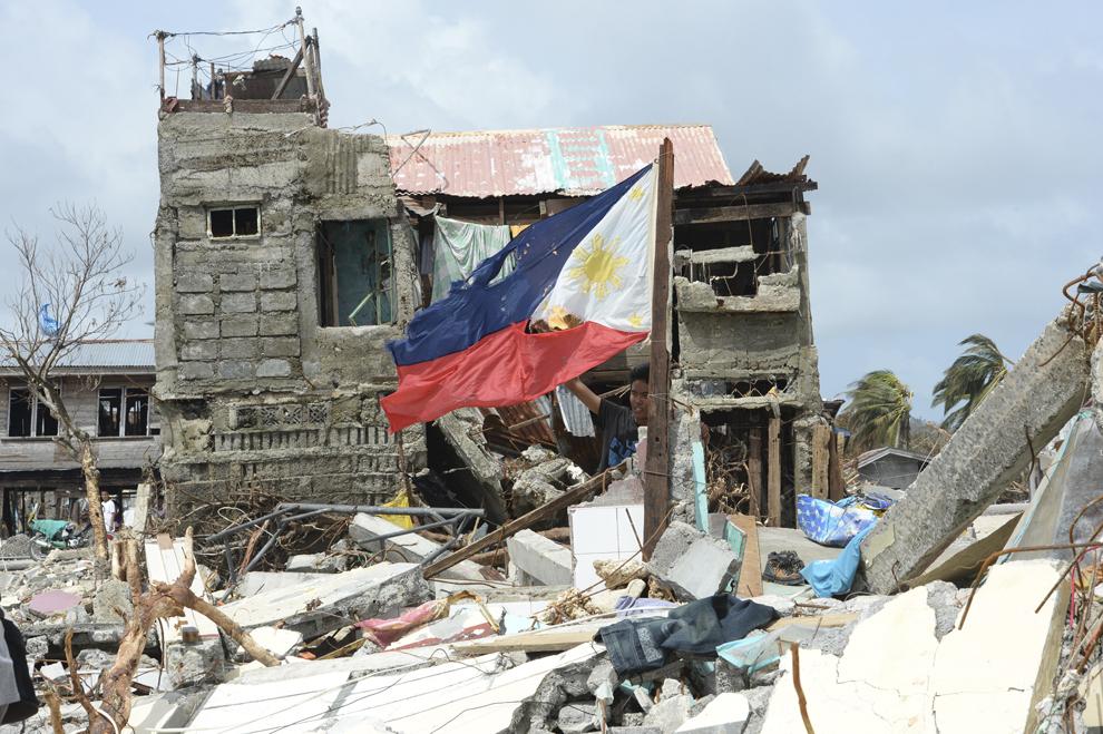 Un barbat ţine în mână un steag distrus, înconjurat de rămăşiţele unei case,  în urma trecerii  super-taifunului Haiyan, în oraşul Hernani, provincia Samar, Filipine, luni, 11 noiembrie 2013.